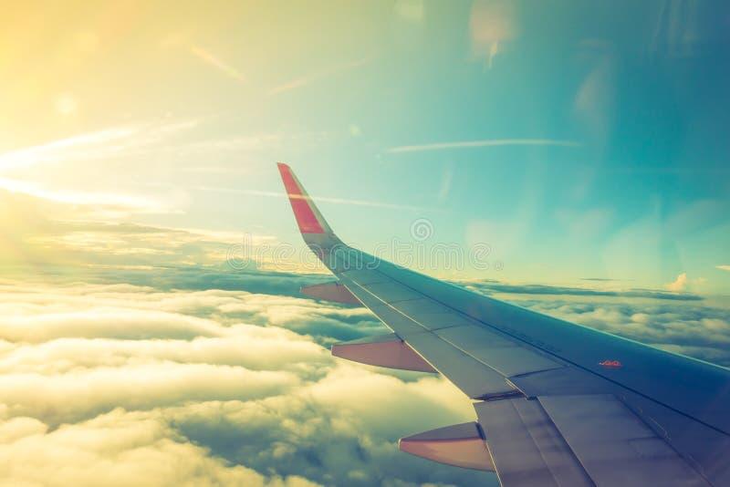 Vleugel van een vliegtuig dat boven de wolken vliegt (Gefiltreerd beeld PR royalty-vrije stock foto