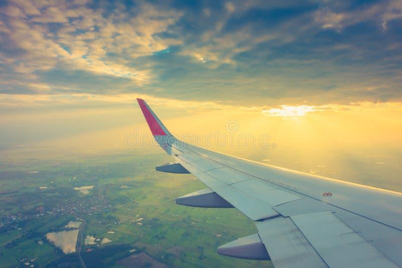 Vleugel van een vliegtuig die boven de wolken bij zonsondergang vliegen (Filter stock foto