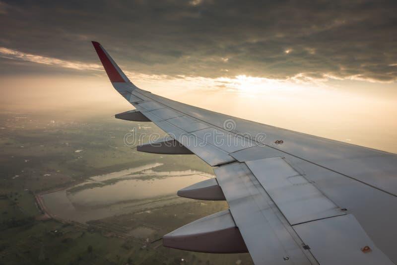 Vleugel van een vliegtuig die boven de wolken bij zonsondergang vliegen (Filter stock fotografie