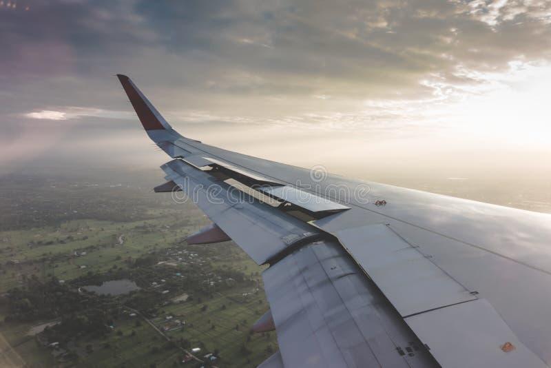 Vleugel van een vliegtuig die boven de wolken bij zonsondergang vliegen (Filter royalty-vrije stock foto