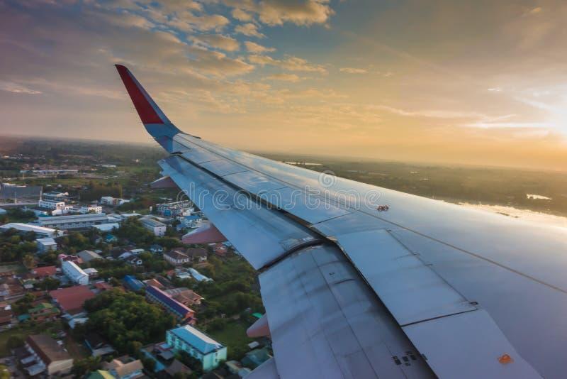 Vleugel van een vliegtuig die boven de wolken bij zonsondergang vliegen (Filter royalty-vrije stock foto's