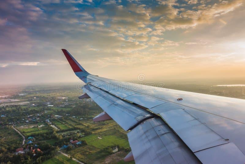 Vleugel van een vliegtuig die boven de wolken bij zonsondergang vliegen (Filter royalty-vrije stock afbeeldingen