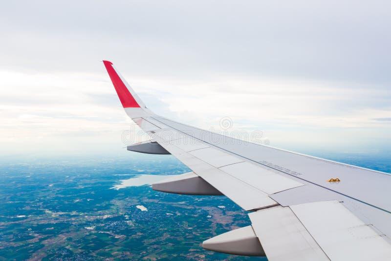 Vleugel van een vliegtuig die boven de wolken op witte achtergrond vliegen royalty-vrije stock afbeeldingen