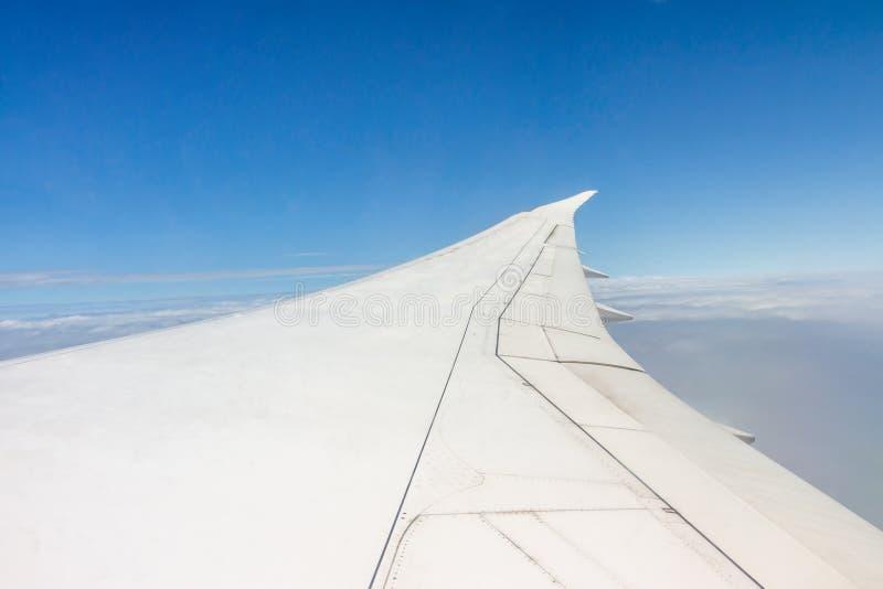 Vleugel van een vliegtuig die in de hemel vliegen stock fotografie