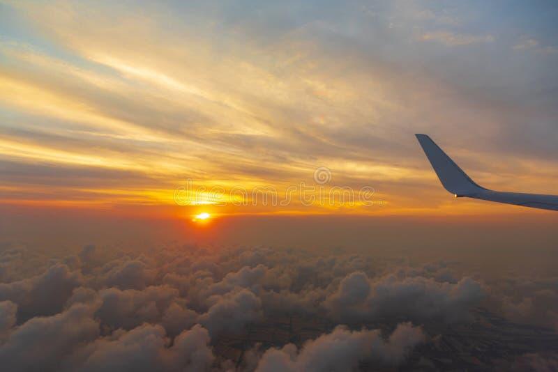 Vleugel van het luchtvliegtuig op het overzees van de hemelachtergrond van de wolkenzonsondergang van venstervliegtuig royalty-vrije stock afbeeldingen