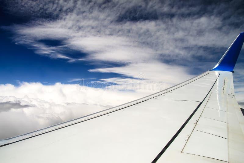 Vleugel van het vliegtuig tegen de hemel en de mooie vlokschuimwolken Mening door een vliegtuigvenster stock foto