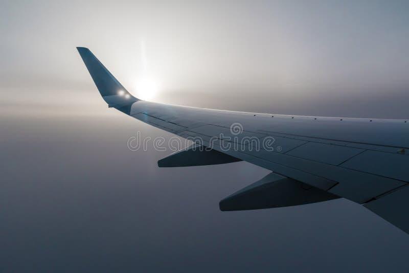 Vleugel van vliegtuig en zon in mist royalty-vrije stock afbeelding
