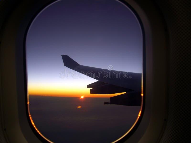 Vleugel van vliegtuig met zonsondergang stock foto