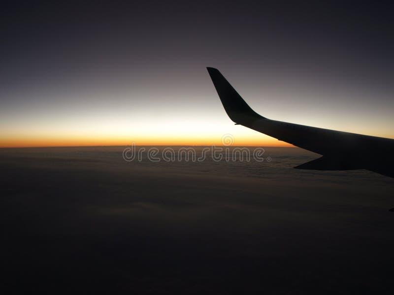 Vleugel van vliegtuigen die bij dageraad vliegen stock afbeelding