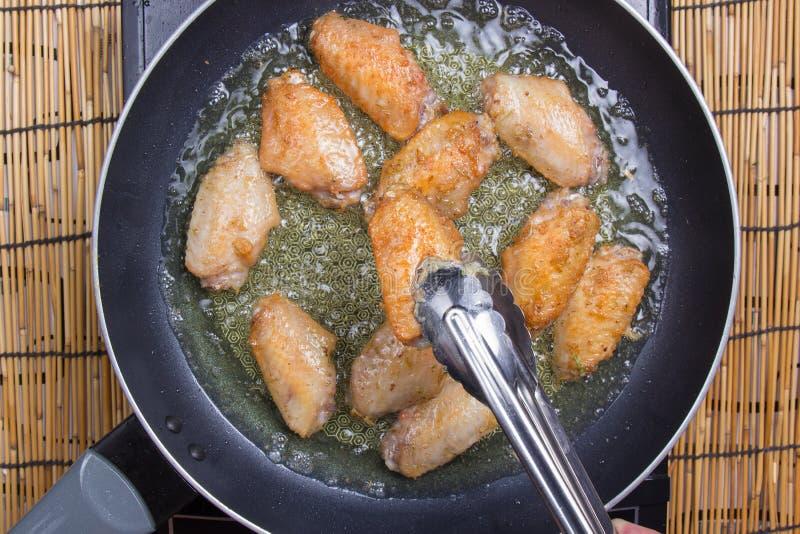 Vleugels van de chef-kok de bradende kip in pan royalty-vrije stock afbeeldingen