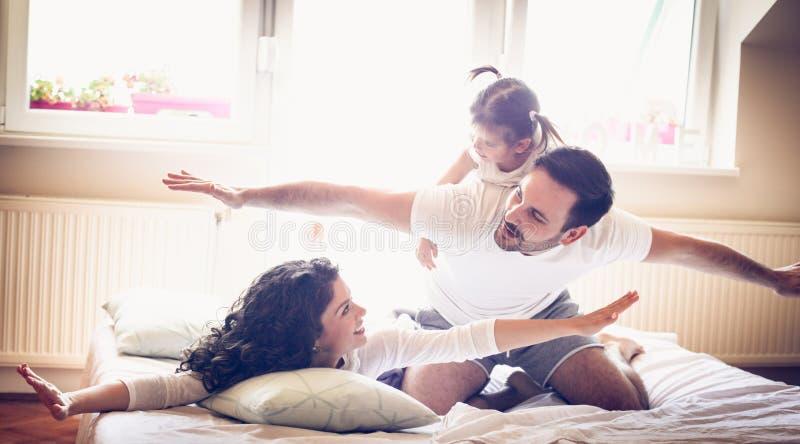 Vlieg in bed De jonge ouders hebben spel met meisje stock afbeeldingen