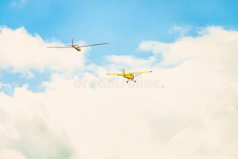 Vliegend in een heldere bewolkte hemel, trekt een geel klein sportenvliegtuig met een lichte motor, de kabel door zweefvliegtuigv stock afbeeldingen