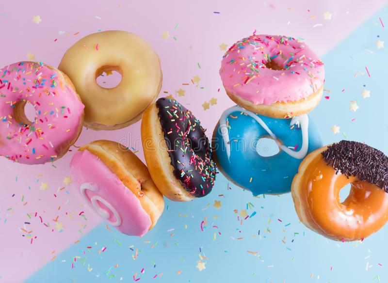 Vliegende doughnuts op blauw stock fotografie