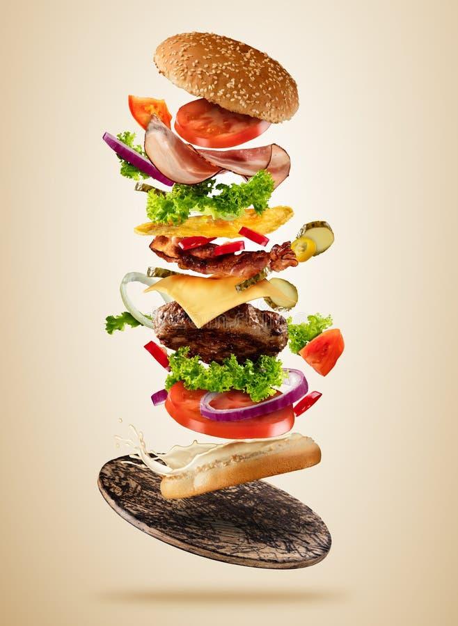 Vliegende hamburgeringrediënten boven houten raad op bruine achtergrond stock afbeeldingen