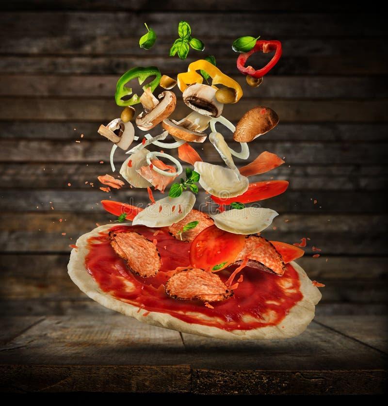 Vliegende ingrediënten met pizzadeeg, op houten achtergrond royalty-vrije stock afbeeldingen