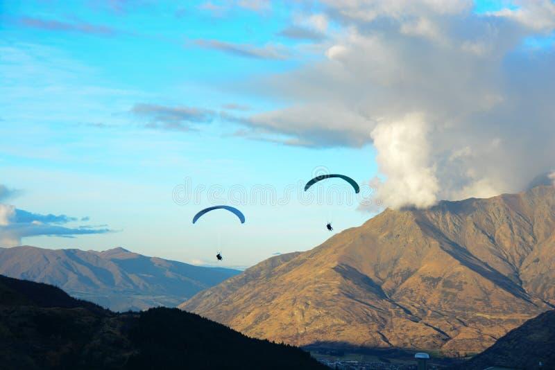 Vliegende mensen door de bergen stock afbeelding