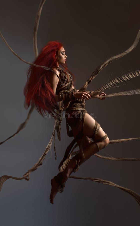 Vliegende mooie rode haired vrouw die door kabels bounding stock afbeelding