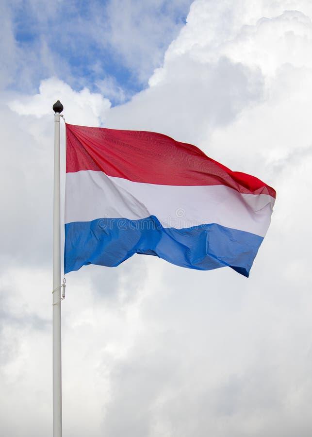 Vliegende Nederlandse vlag, rode witte en blauwe, gehesen vlag royalty-vrije stock foto's