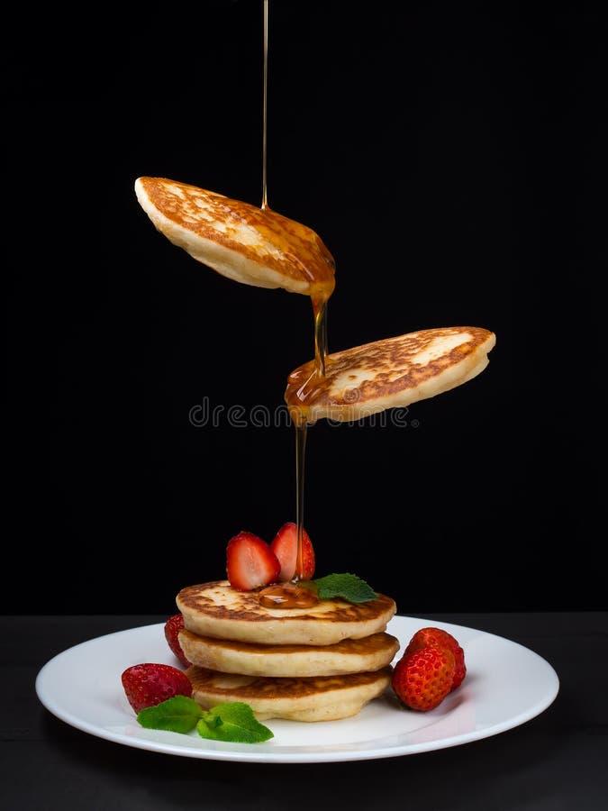 Vliegende pannekoeken met honing en aardbeien royalty-vrije stock foto's