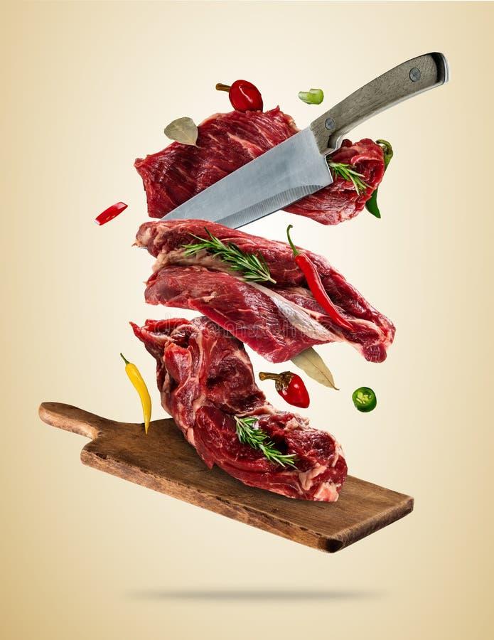 Vliegende ruwe lapjes vlees met ingrediënten, het concept van de voedselvoorbereiding stock foto's