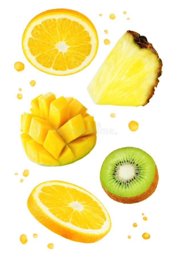 Vliegende Sinaasappelen met mango, kiwi, ananas en sap` s nevel stock afbeeldingen