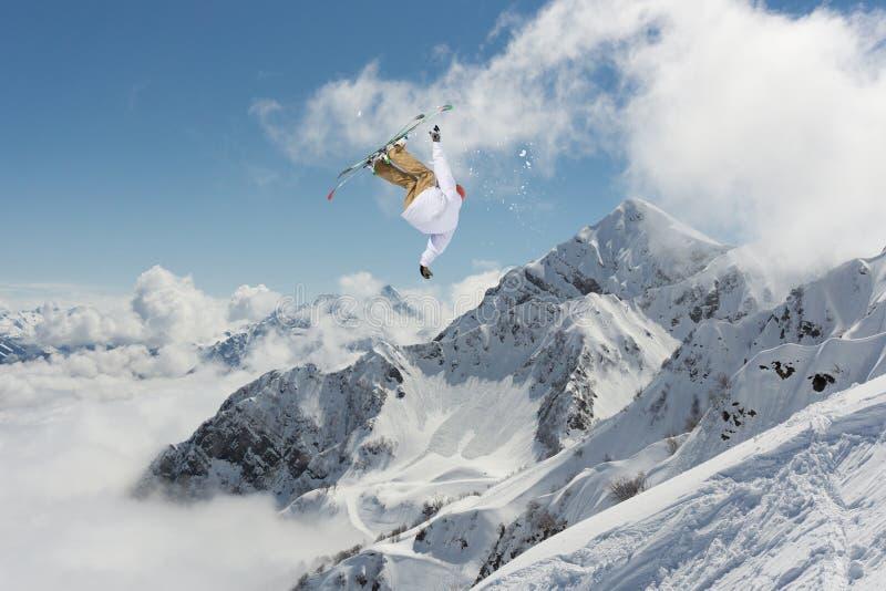 Vliegende skiër op sneeuwbergen Extreme de wintersport, alpiene ski stock afbeeldingen