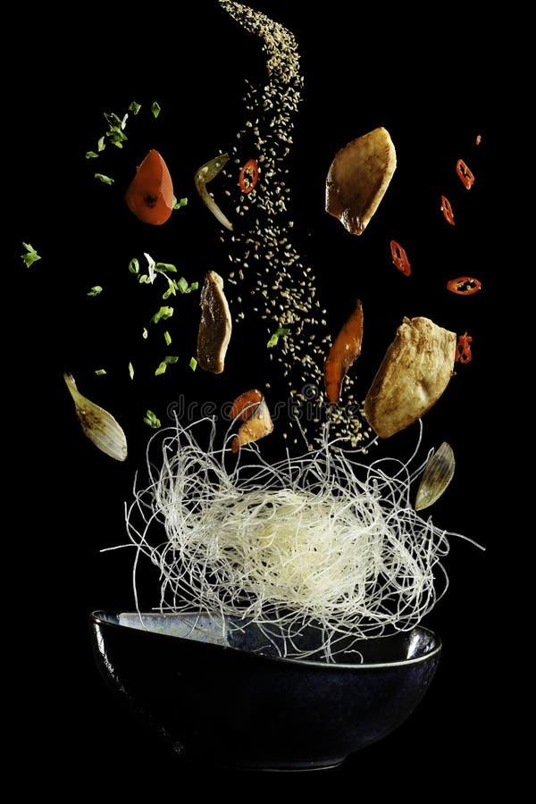 Vliegende wok met kip en kruiden Concept voedselvoorbereiding op lage ernstwijze, voedsellevitatie Gescheiden op zwarte royalty-vrije stock afbeeldingen