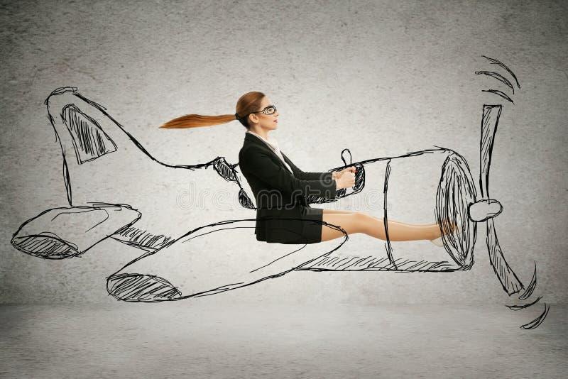 Vliegeniersvrouw met sjaal en glazen die ontworpen vliegtuig vliegen stock afbeeldingen
