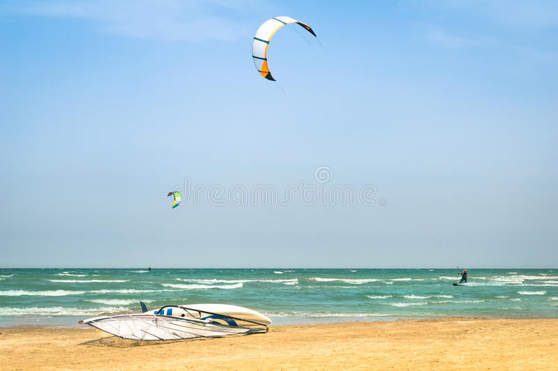Vlieger die in winderig strand met windsurfraad surfen royalty-vrije stock fotografie