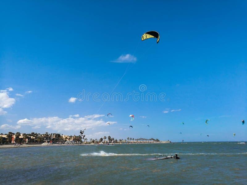 Vlieger inschepende sportman hoog met vlieger en kiteboard in laarzen in de blauwe hemel vliegen, actieve sporten en levensstijl  royalty-vrije stock afbeelding