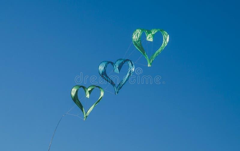 Vlieger met met drie groene en blauwe harten die in de hemel vliegen royalty-vrije stock fotografie