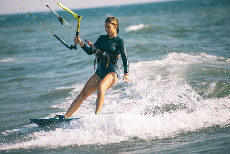 Vlieger surfend meisje in sexy zwempak met vlieger in blauwe overzees stock afbeeldingen