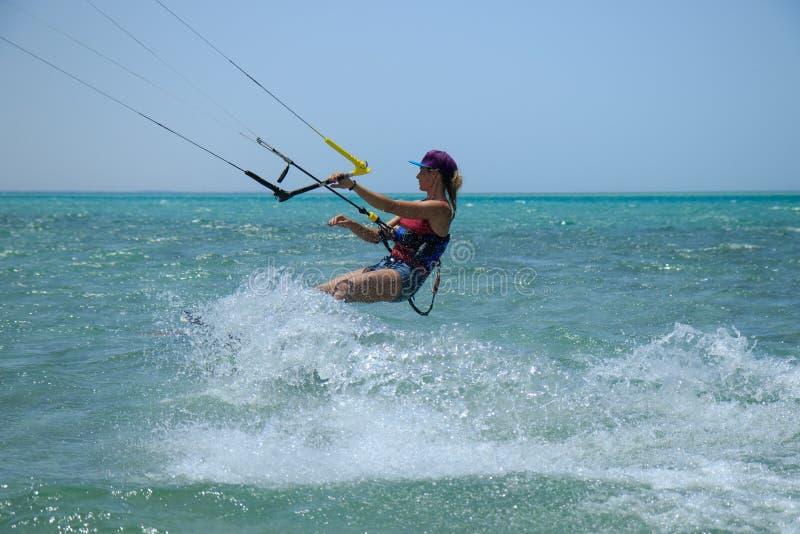 Vlieger surfend meisje in zwempak met vlieger in hemel aan boord in blauwe overzeese berijdende golven met waterplons Recreatieve royalty-vrije stock foto