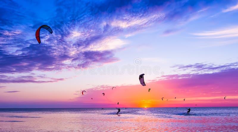 Vlieger-surft tegen een mooie zonsondergang Vele silhouetten van uitrusting stock fotografie