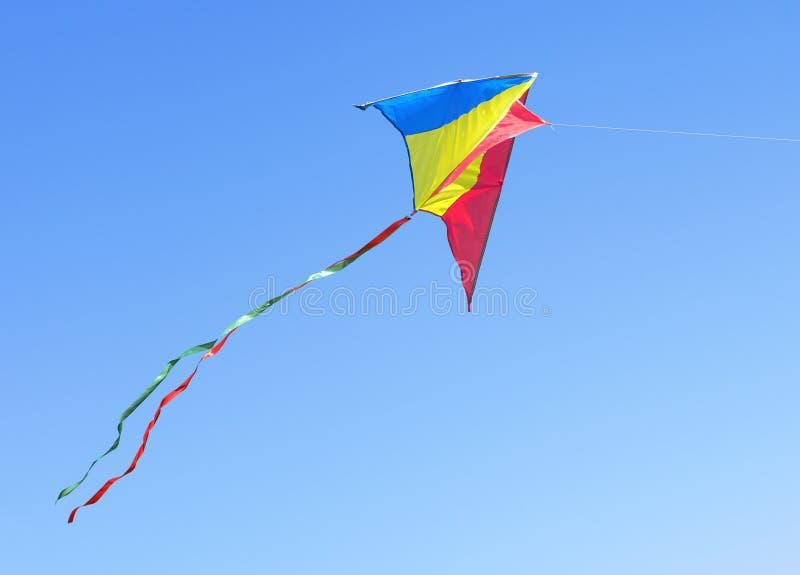Vlieger tegen de blauwe hemel stock afbeelding