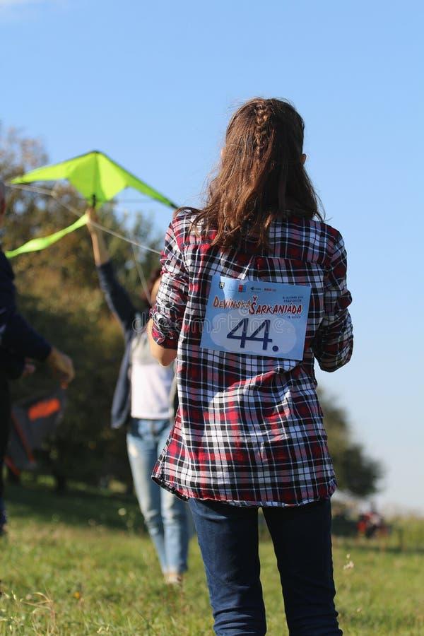 Vliegerfestival - youg meisje die op haar vader met een vlieger letten stock afbeelding