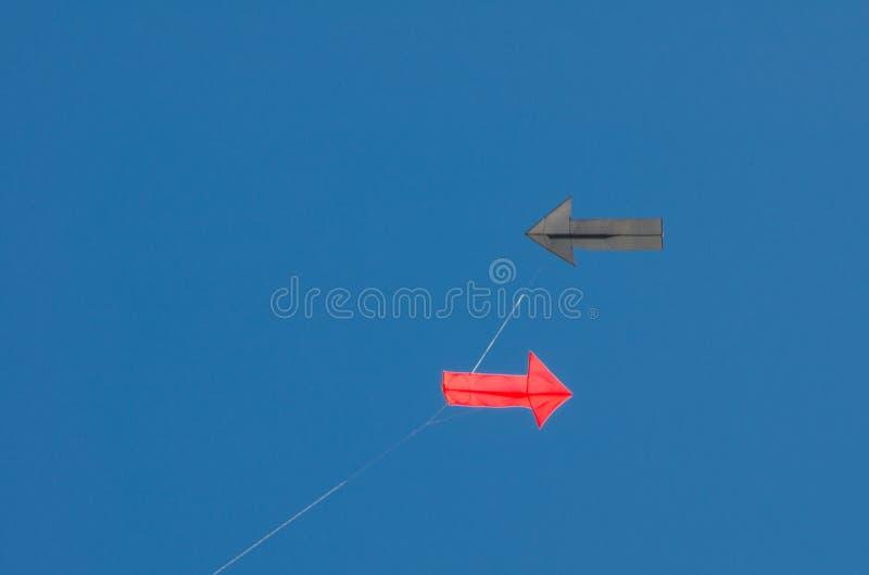 Vliegerontwerp in Rode pijl en het Zwarte die pijl vliegen op blauwe hemelachtergrond wordt geïsoleerd royalty-vrije stock foto