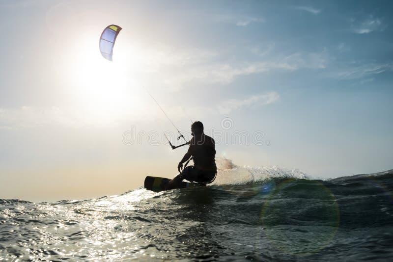 Vliegersurfer die voor de zonsondergang varen stock fotografie