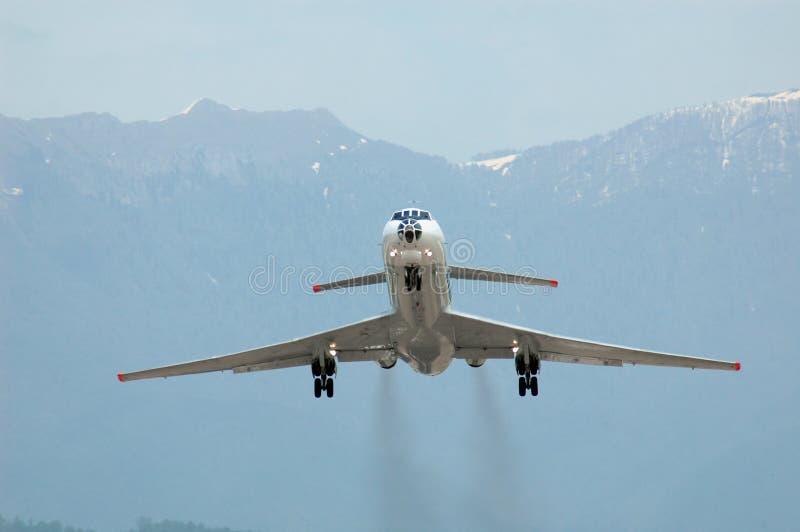 Vliegtuig bij start op bergachtergrond stock foto