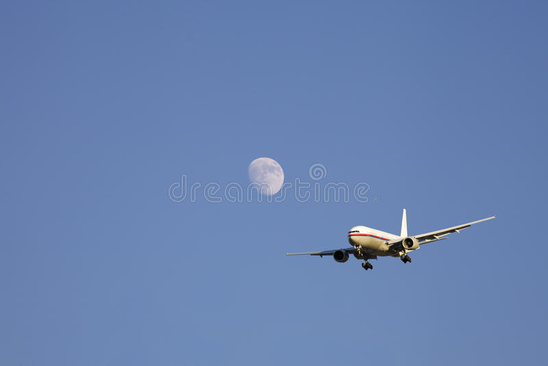 Vliegtuig dat voorbij de maan vliegt royalty-vrije stock foto