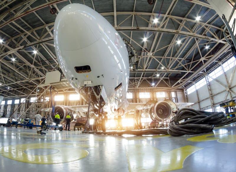 Vliegtuig in de hangaar voor onderhoud, de mening van de bodemneus royalty-vrije stock afbeeldingen