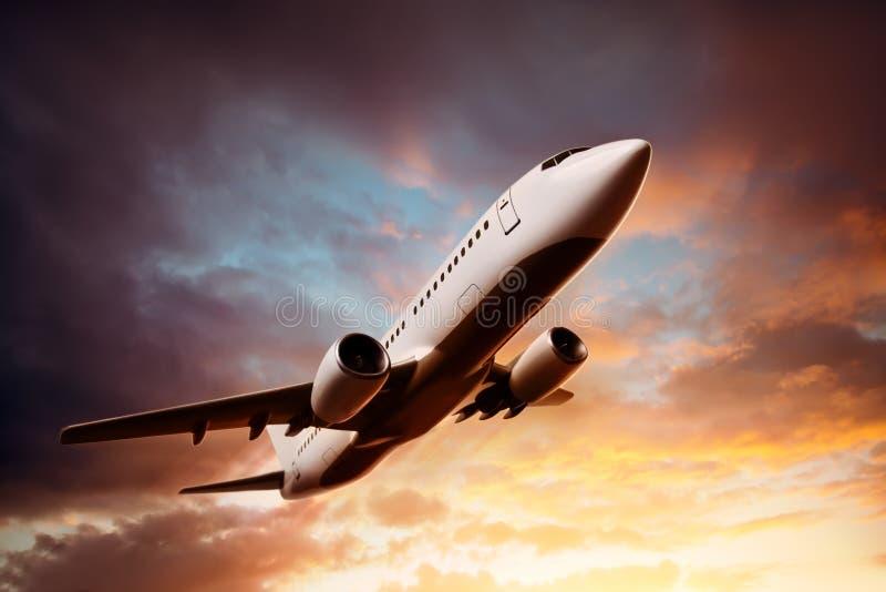 Vliegtuig in de hemel bij zonsondergang stock foto's
