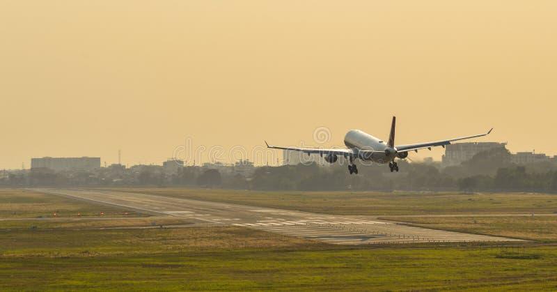 Vliegtuig die bij de luchthaven op zonsondergang landen stock afbeeldingen