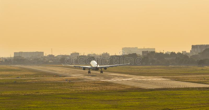 Vliegtuig die bij de luchthaven op zonsondergang landen stock foto's