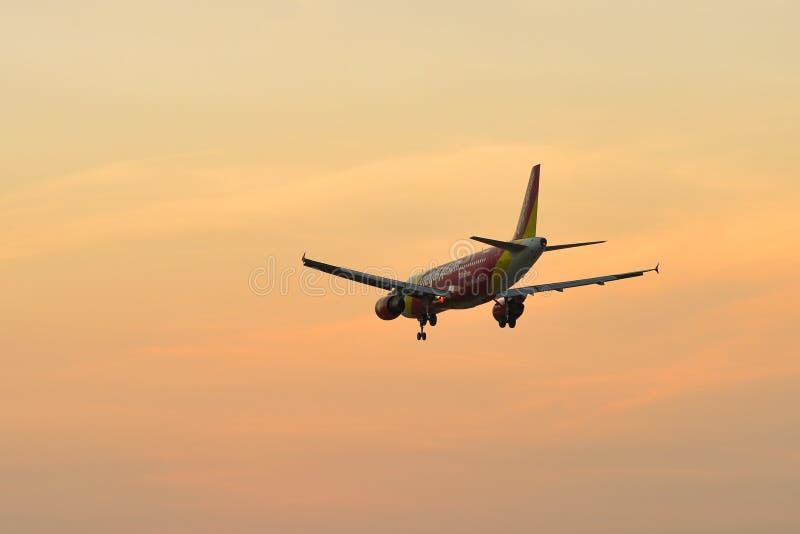 Vliegtuig die bij de luchthaven op zonsondergang landen stock fotografie