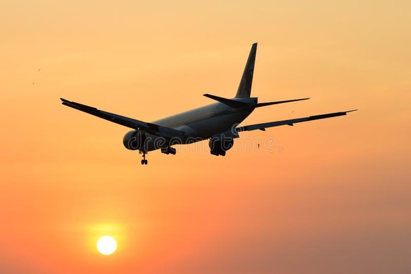 Vliegtuig die bij de luchthaven op zonsondergang landen stock foto