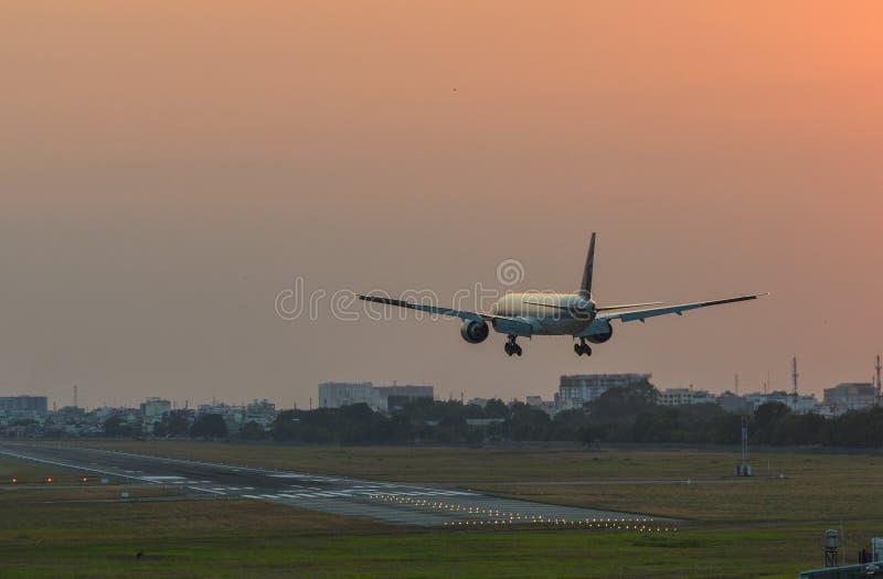 Vliegtuig die bij de luchthaven op zonsondergang landen stock afbeelding
