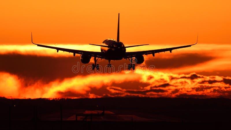 Vliegtuig die bij Otopeni luchthaven tijdens zonsondergang met rode hemel bevlekken royalty-vrije stock afbeelding