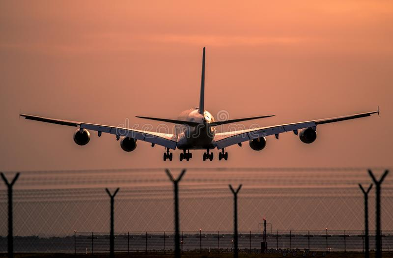 Vliegtuig die bij zonsondergang landen royalty-vrije stock afbeelding