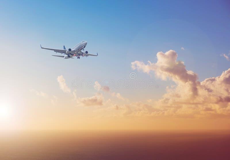 Vliegtuig die boven oceaan met de achtergrond van de zonsonderganghemel vliegen - trav stock foto's